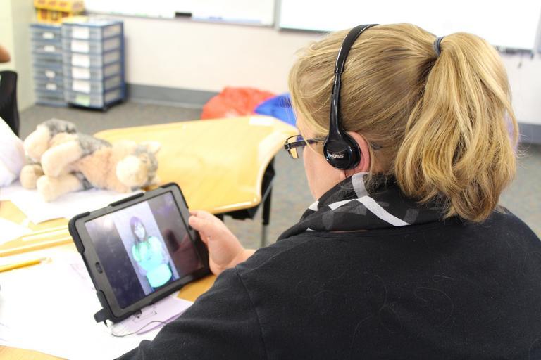 děvče, co komunikuje přes tablet a má sluchátka na uších