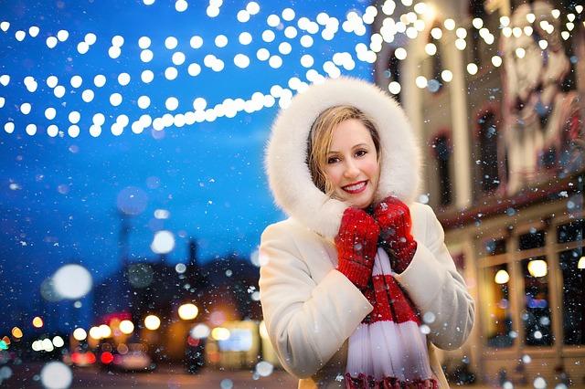 Žena v bílém kožichu stojící ve vánočně vyzdobené ulici