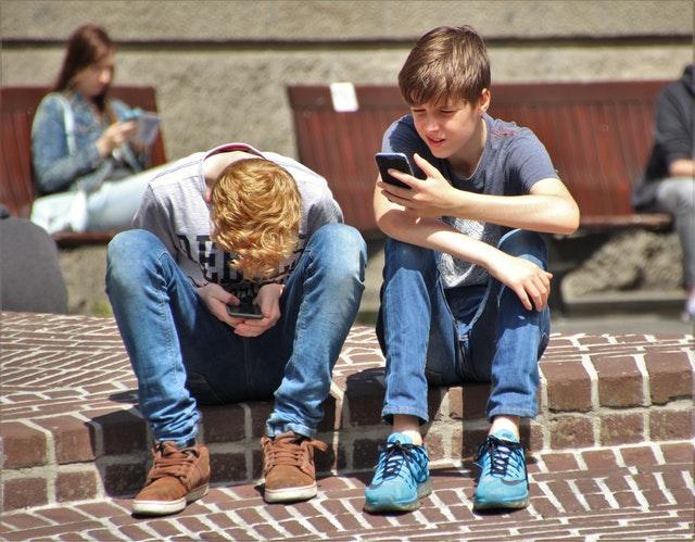 Dva kluci sedící na okraji chodníku držící v rukou mobily