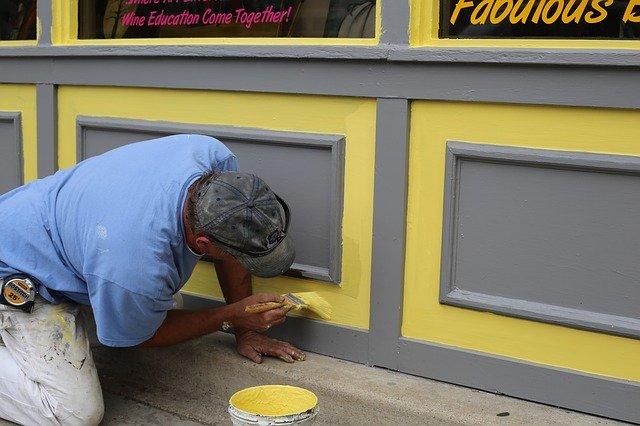 malíř pracující na fasádě domu