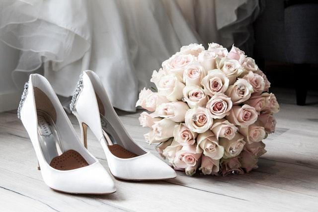 bílé lodičky, vedle svatební kytice z růží, za nimi kousek bílých šatů