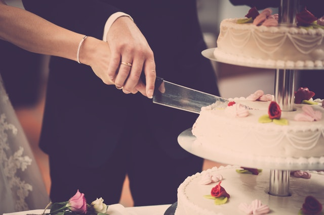 manželé krájí vícepatrový dort